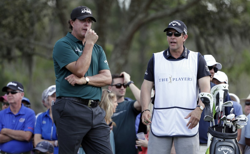 Phil Mickelson, left, listens to his brother and caddie Tim Mickelson as he waits to tee off on the ninth hole during the second round of The Players