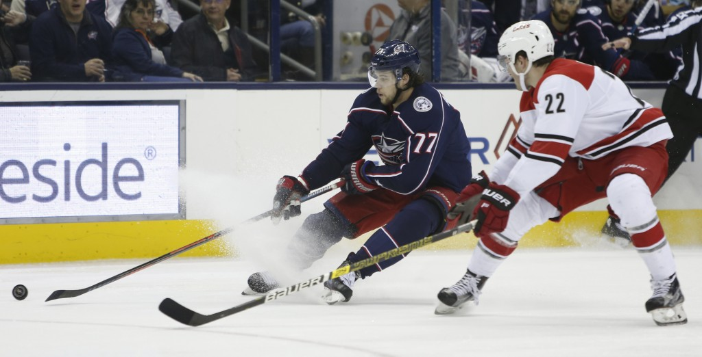 Columbus Blue Jackets' Josh Anderson, left, tries to control the puck up as Carolina Hurricanes' Brett Pesce defends and during the first period of an
