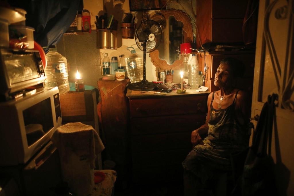 72-year-old Elizabeth Guzman Espitia sits in her windowless room during a blackout in the Santa Cruz of the East neighborhood, in Caracas, Venezuela,