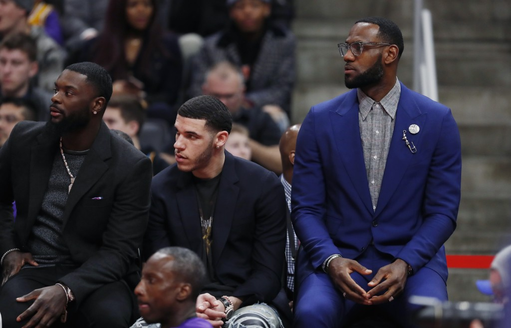 Los Angeles Lakers forward LeBron James, right, sits out the NBA basketball game against the Detroit Pistons with teammate guards Lance Stephenson, le