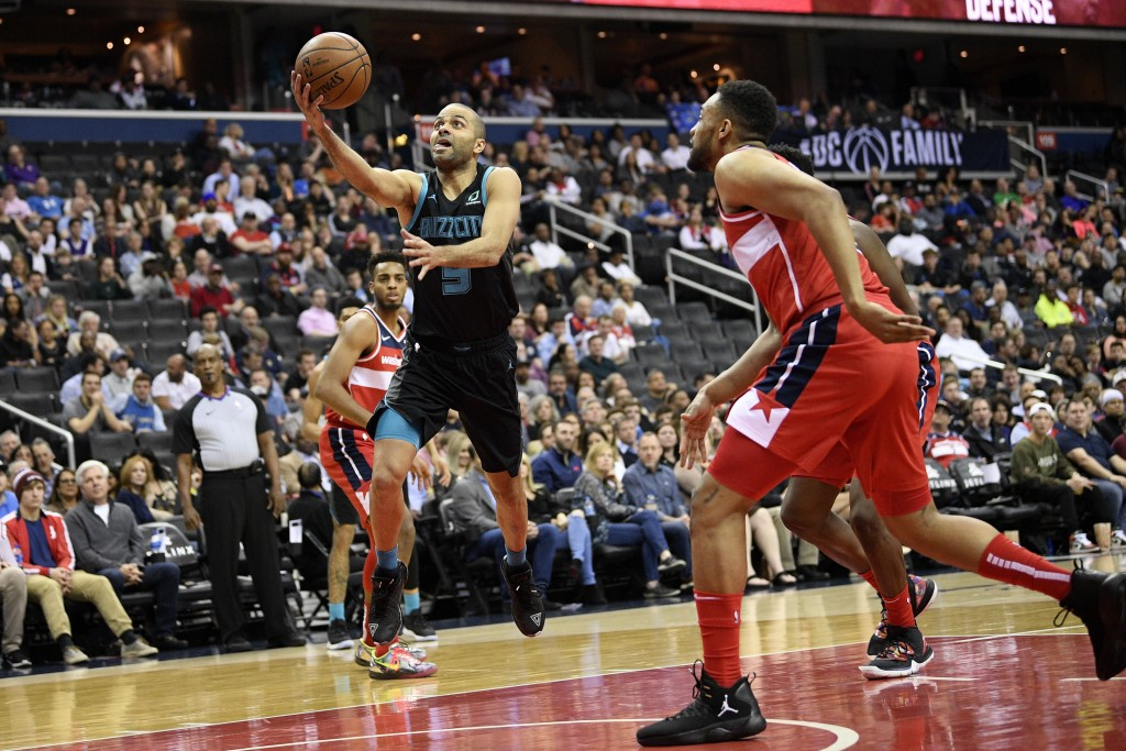 Charlotte Hornets guard Tony Parker (9) goes to the basket against Washington Wizards forward Jabari Parker, right, during the first half of an NBA ba