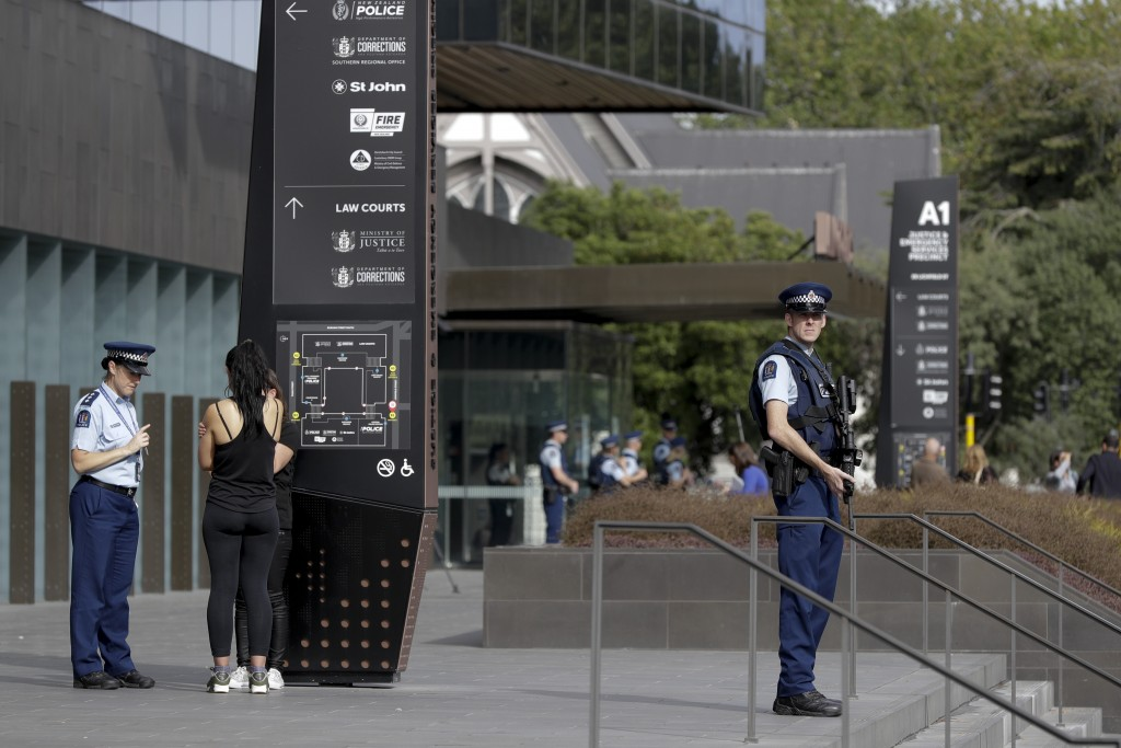 Police stand guard outside the district court building in Christchurch New Zealand Saturday