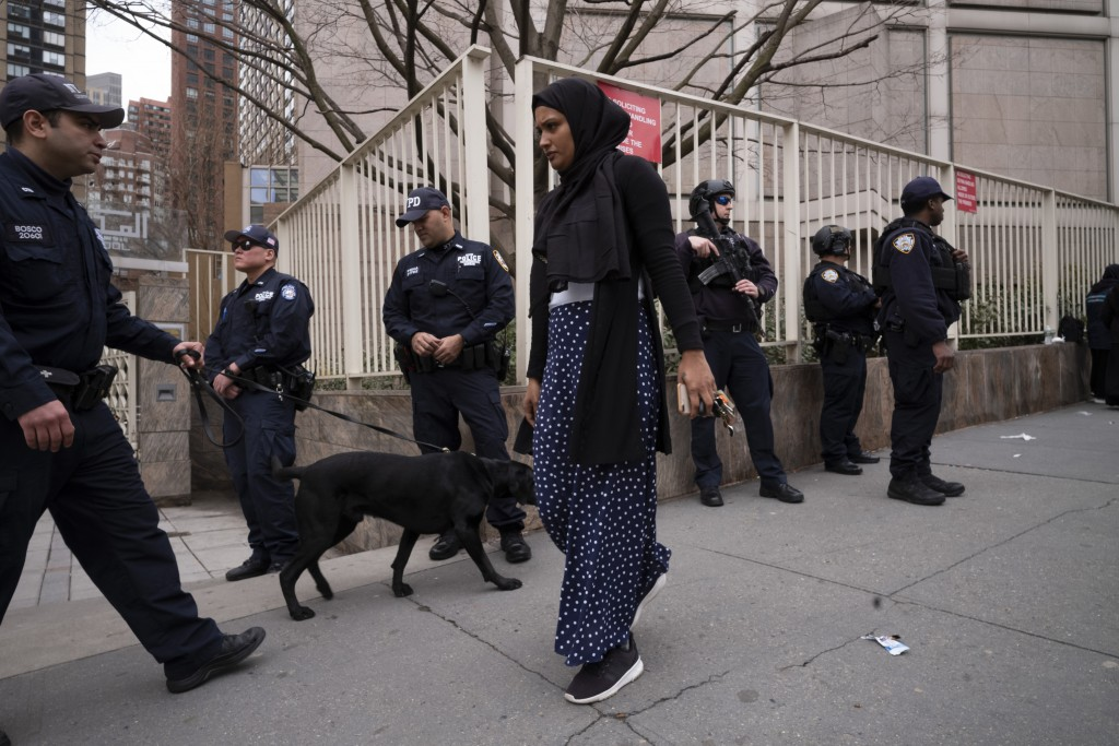 A woman arrives for service at the Islamic Cultural Center of New York under increased police security following the shooting in New Zealand, Friday,