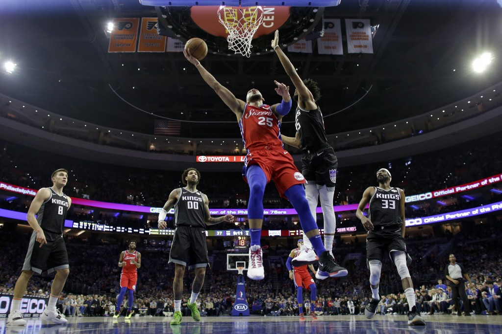 Philadelphia 76ers' Ben Simmons, left, goes up for a shot against Sacramento Kings' Marvin Bagley III during the first half of an NBA basketball game,