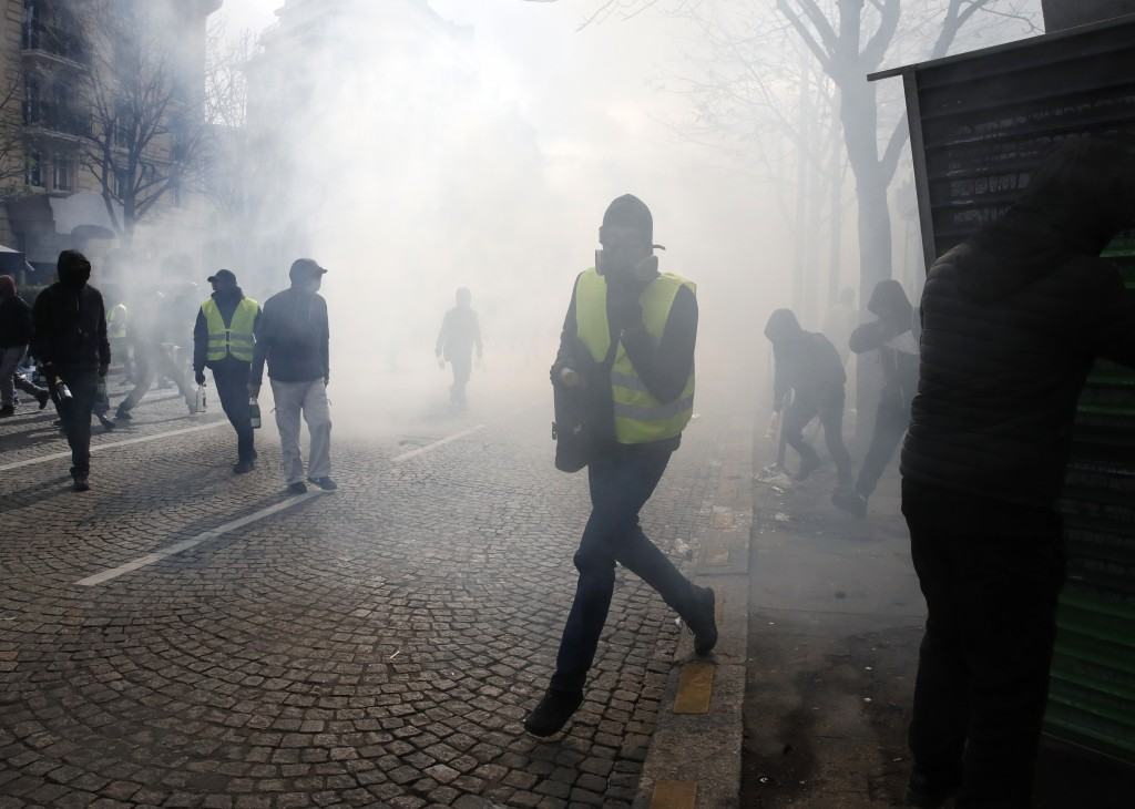 Protesters walk through tear gas during a yellow vests demonstration Saturday, March 16, 2019 in Paris. French yellow vest protesters clashed Saturday