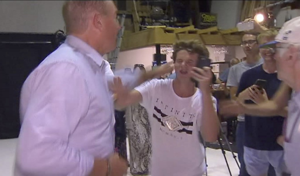 In this image made from video, Senator Fraser Anning swipes at a teenager who broke an egg on his head while he was holding a press conference, Saturd