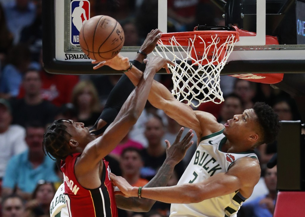 Milwaukee Bucks forward Giannis Antetokounmpo, right, blocks a shot by Miami Heat guard Josh Richardson during the second half of an NBA basketball ga