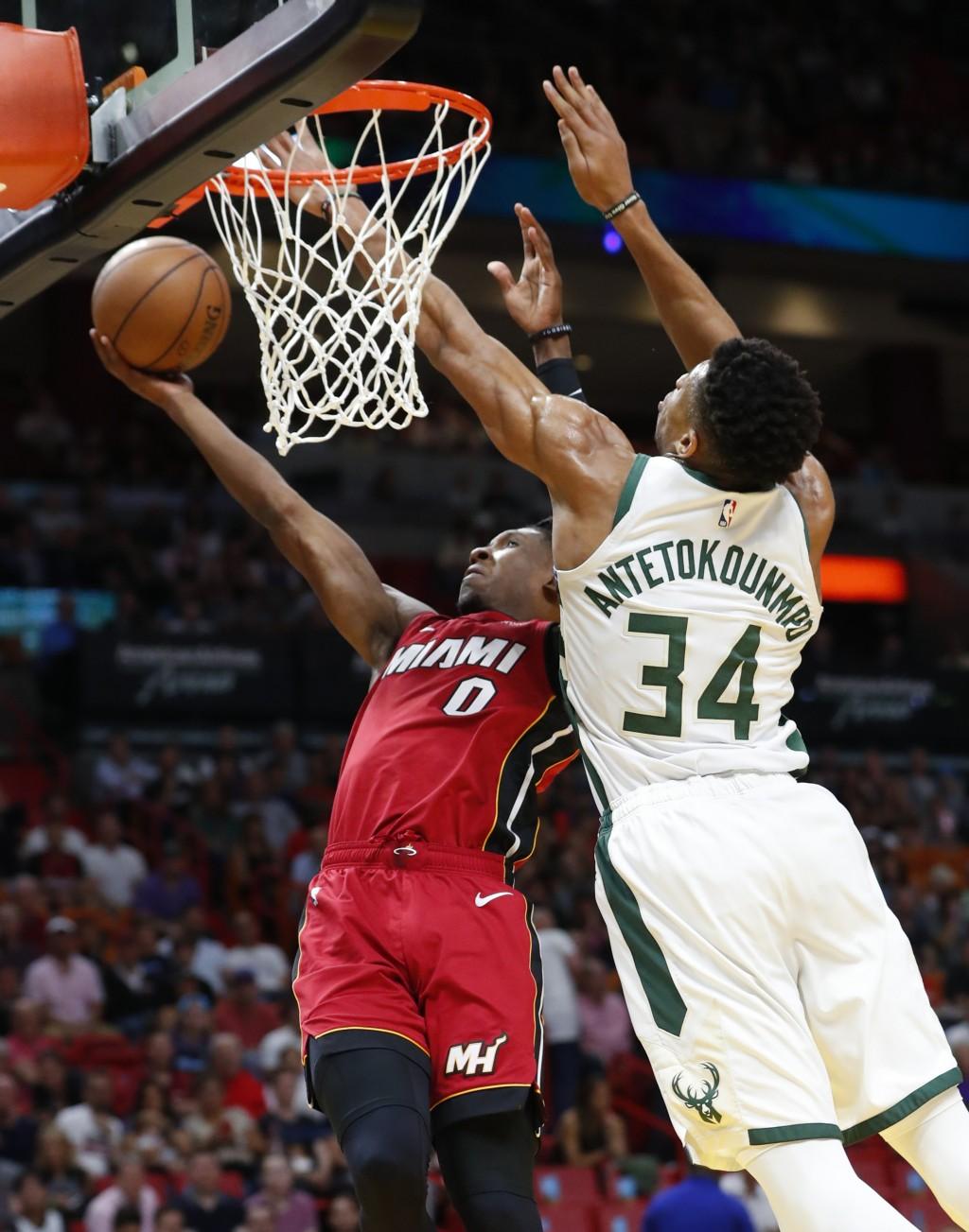 Miami Heat guard Josh Richardson (0) shoots next to Milwaukee Bucks forward Giannis Antetokounmpo (34) during the first half of an NBA basketball game