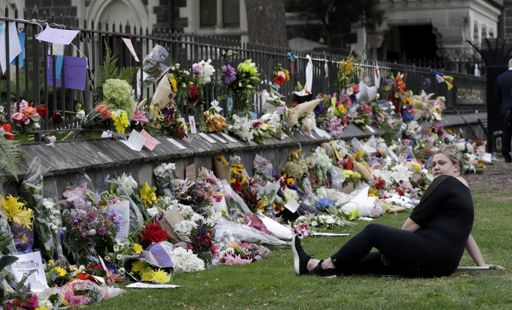 A woman reacts as she sits near the wall with floral tributes at the Botanical Gardens, Saturday, March 16, 2019, Christchurch, New Zealand. (AP Photo