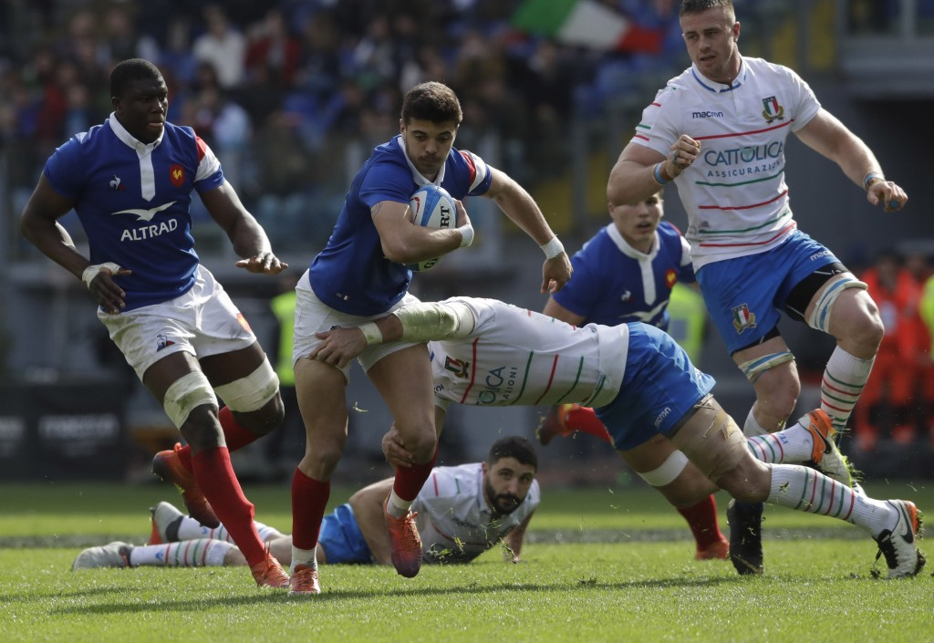 Italy's Sergio Parisse, right, tackles France's Romain Ntamack, center and France's Yacouba Camara, left, during the Six Nations rugby union internati