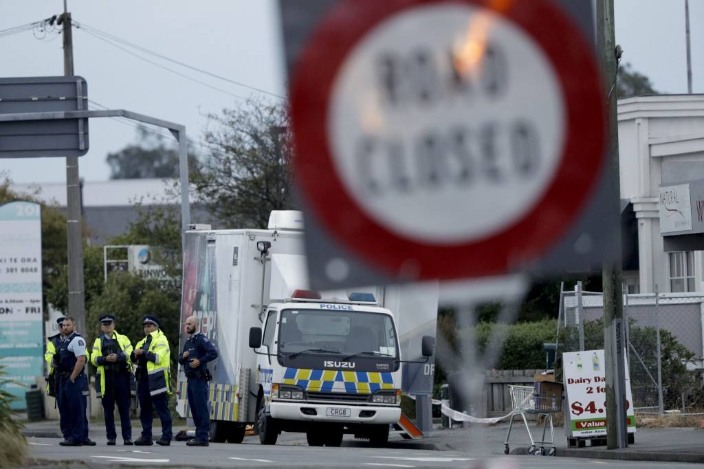 Police gather outside the Linwood mosque, site of one of the mass shootings at two mosques in Christchurch, New Zealand, Saturday, March 16, 2019. (AP