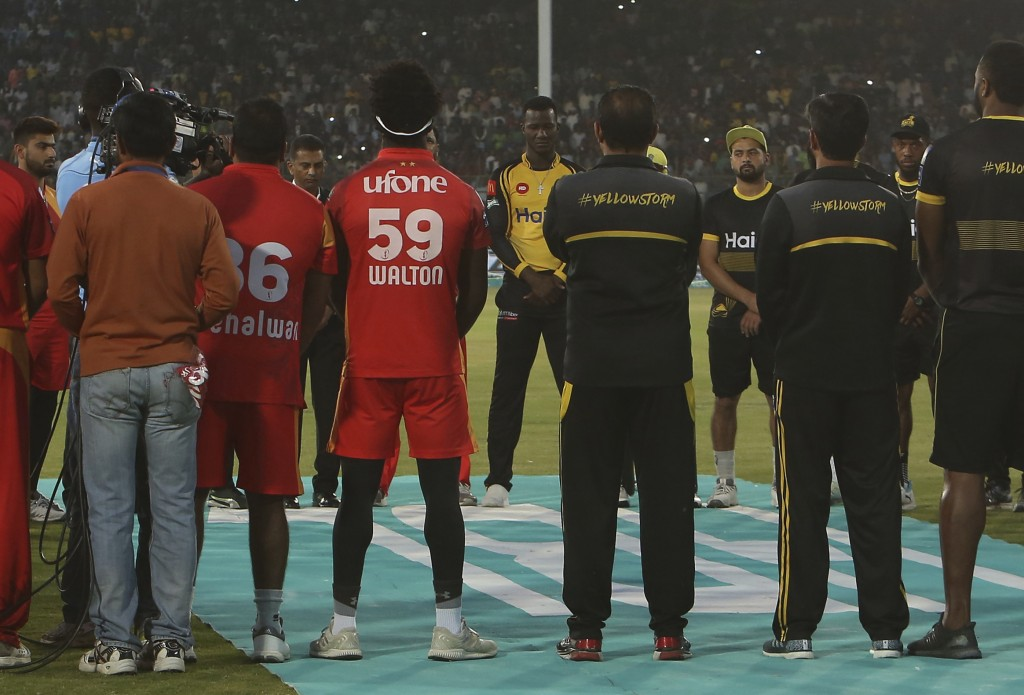Darren Sammy, center, facing camera, joins other players and officials of Islamabad United and Peshawar Zalmi to observe a minute silence at National