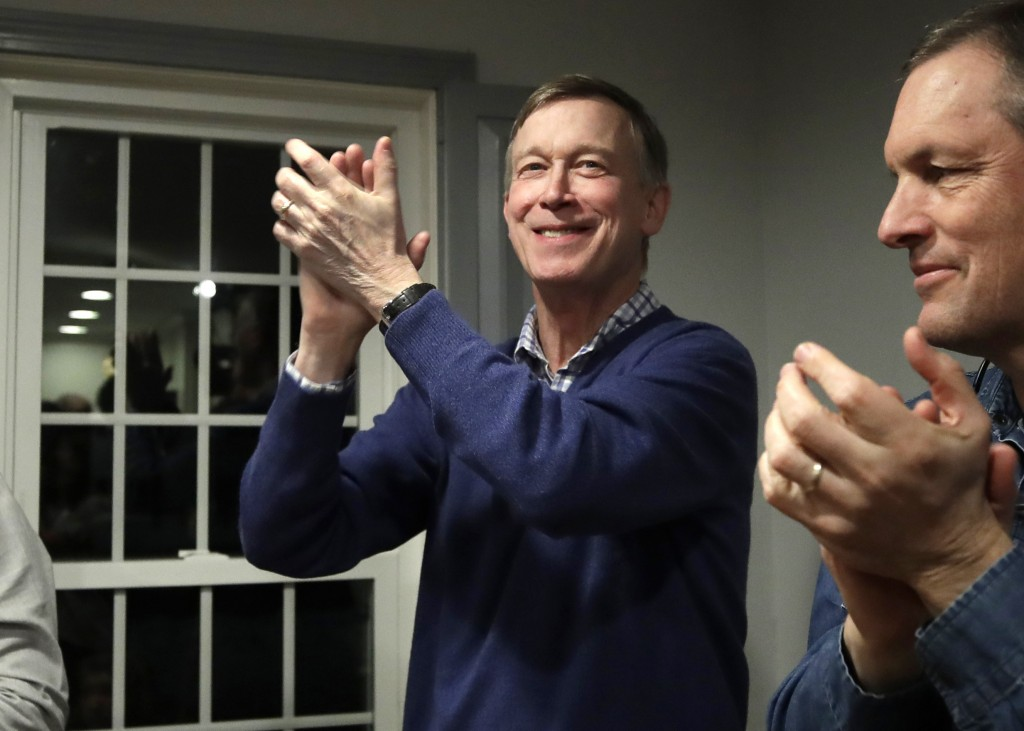 FILE - In this Feb. 13, 2019, file photo, former Colorado Gov. John Hickenlooper, left, applauds at a campaign house party in Manchester, N.H. While t