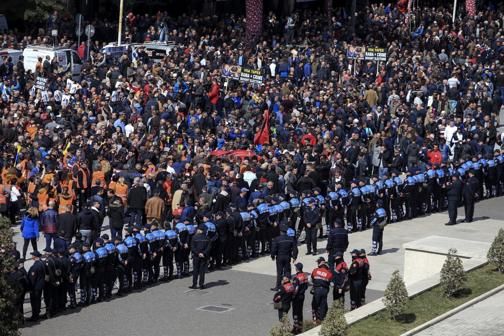 Protesters gather outside the Prime Minister's office during an anti-government rally in Tirana, Albania, Saturday, March 16, 2019. Thousands of suppo