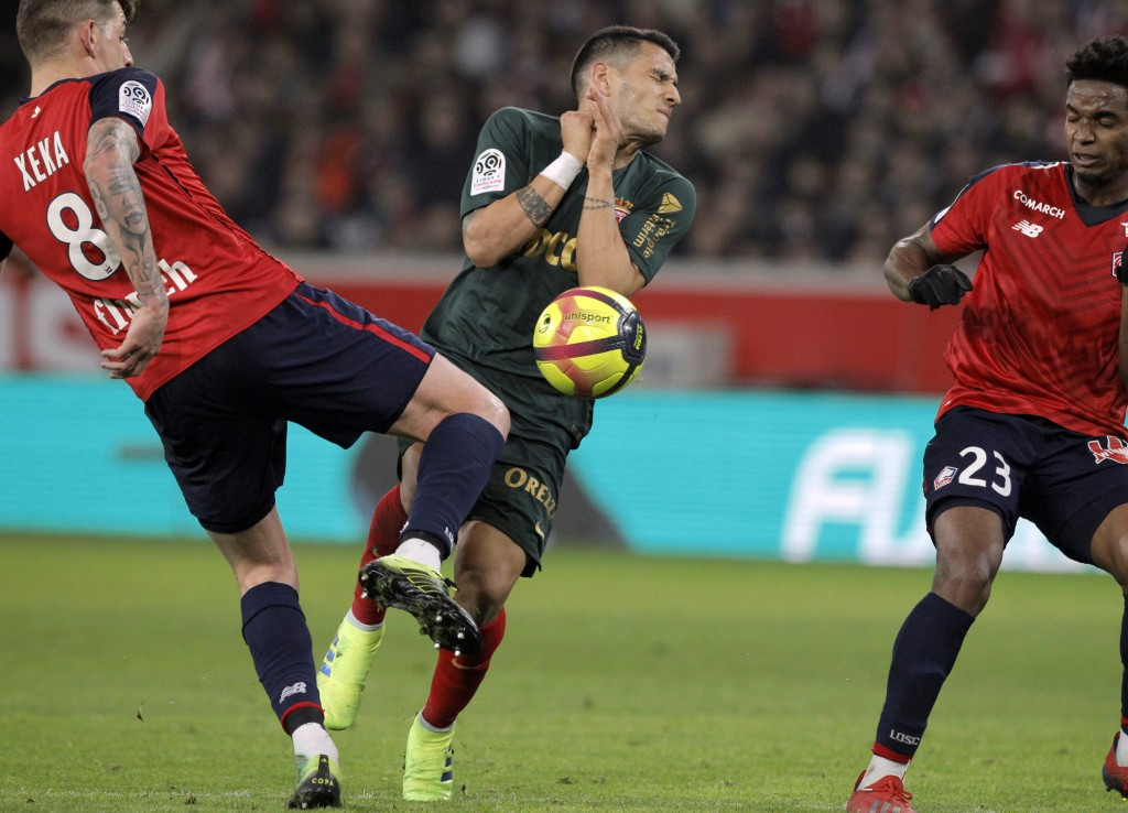 Lille's Xeka, left, and Monaco's Aleksandr Golovin, center, challenge for the ball  during the French League One soccer match between Lille and Monaco
