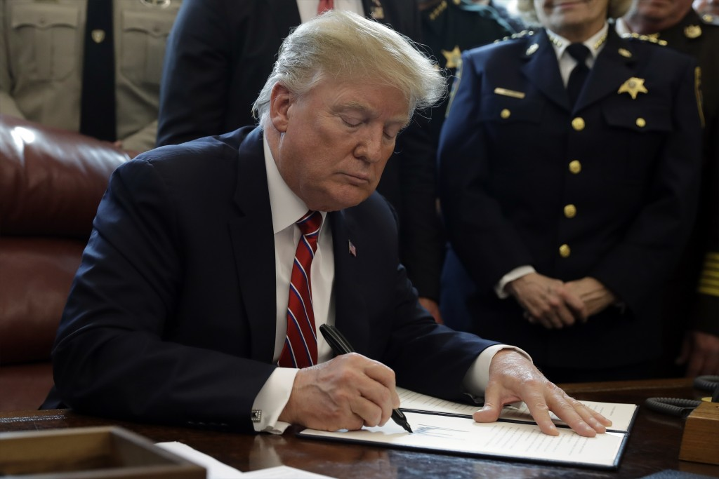 President Donald Trump signs the first veto of his presidency in the Oval Office of the White House, Friday, March 15, 2019, in Washington. Trump issu