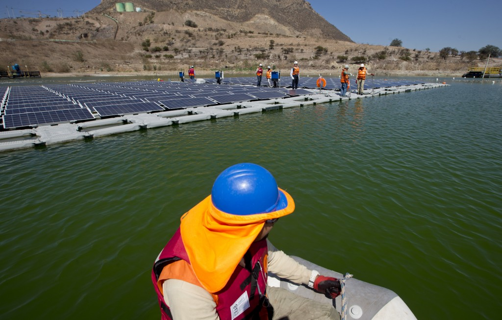A worker on a boat approaches a floating island of solar panels at Los Bronces mine, about 65 kilometers (approximately 40 miles) from Santiago, Chile