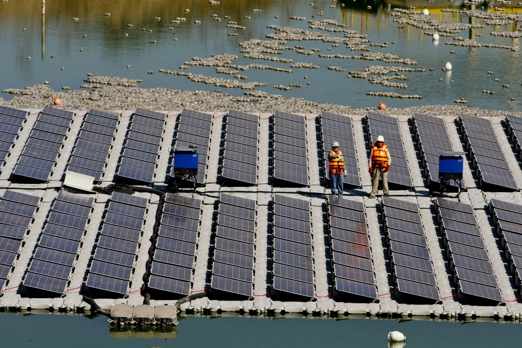 Workers stand on a floating island of solar panels on a pond at Los Bronces mine, about 65 kilometers (approximately 40 miles) from Santiago, Chile, T