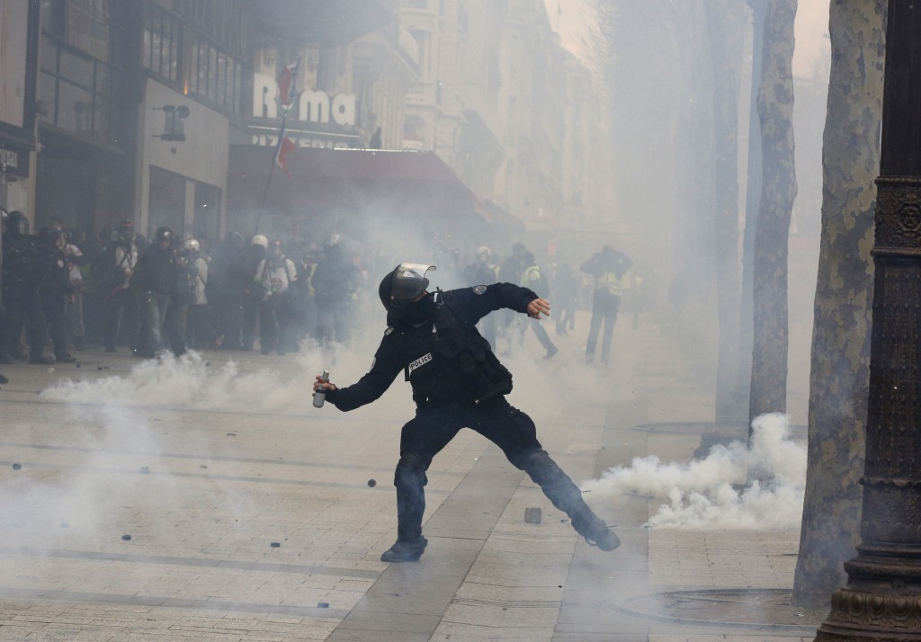A riot police officer throws a tera gas canister onto protesters during a yellow vests demonstration on the Champs Elysees avenue Saturday, March 16,