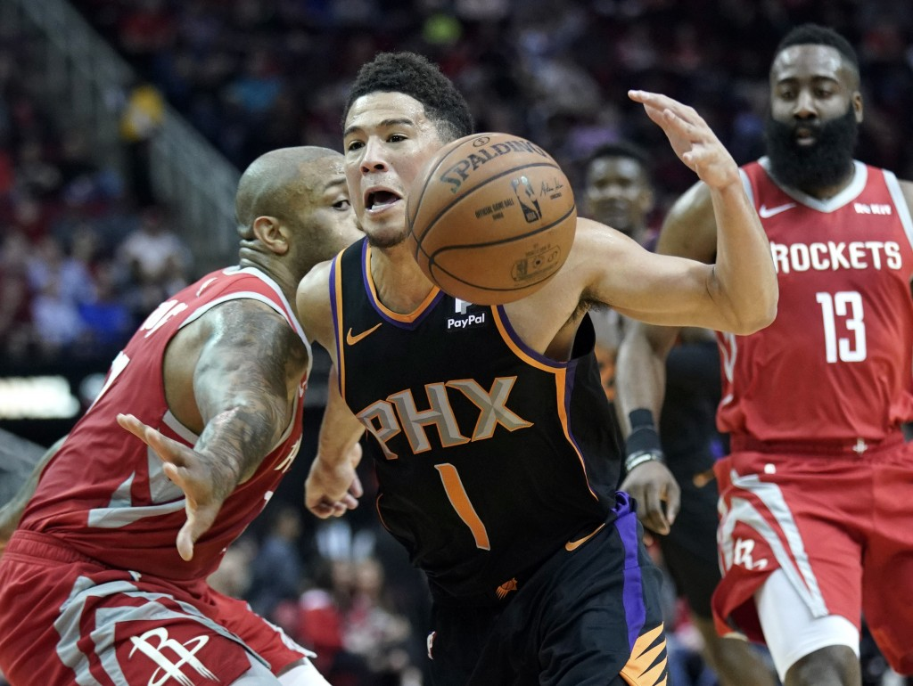 Phoenix Suns' Devin Booker (1) drives past Houston Rockets' PJ Tucker, left, during the first half of an NBA basketball game Friday, March 15, 2019, i
