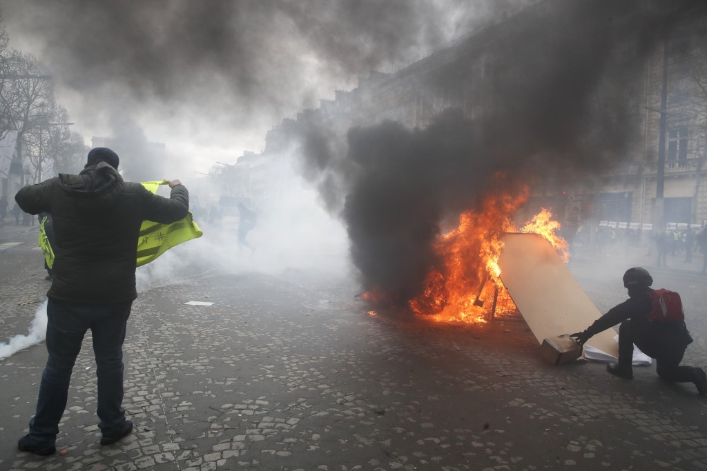 Yellow vests protesters set a burricade afire on the Champs Elysees avenue Saturday, March 16, 2019 in Paris. French yellow vest protesters clashed Sa