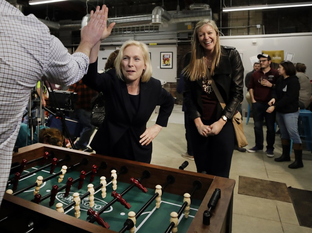 Democratic presidential candidate Sen. Kirsten Gillibrand, D-N.Y., high-fives a foosball opponent as partner Casey Leach of Manchester, N.H., laughs a