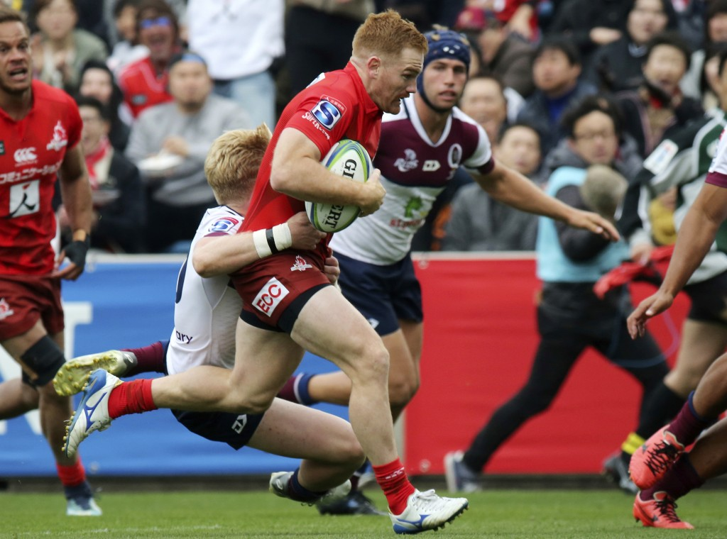 Jamie Booth of Sunwolves is tackled by Reds during their Super Rugby match in Tokyo, Saturday, March 16, 2019. (AP Photo/Koji Sasahara)