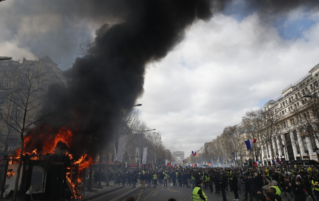 A news stand burns during a yellow vests demonstration on the Champs Elysees avenue Saturday, March 16, 2019 in Paris. French yellow vest protesters c