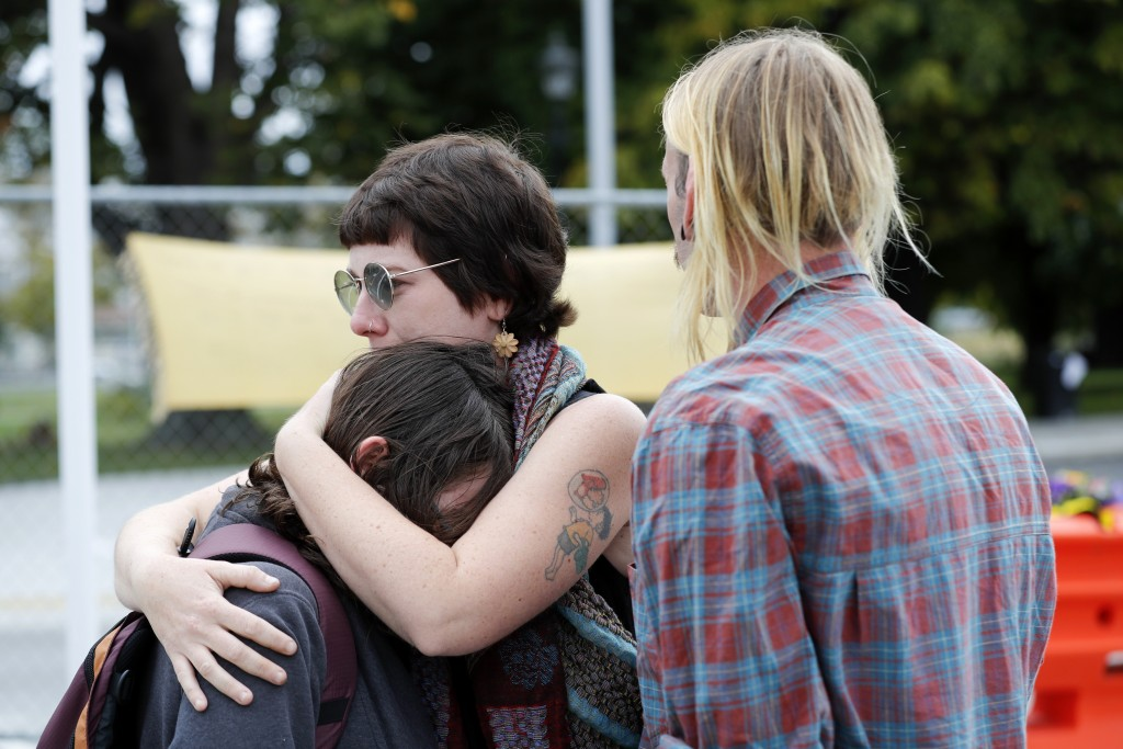 Mourners react as they pay their respects at a makeshift memorial outside Christchurch hospital in Christchurch, New Zealand, Saturday, March 16, 2019