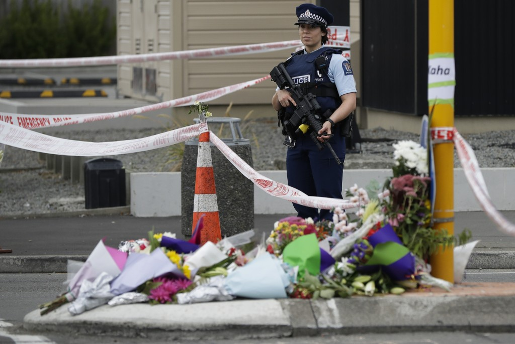 Police stand by a collection of flowers near the Linwood Mosque in Christchurch, New Zealand, Saturday, March 16, 2019, where one of the two mass shoo