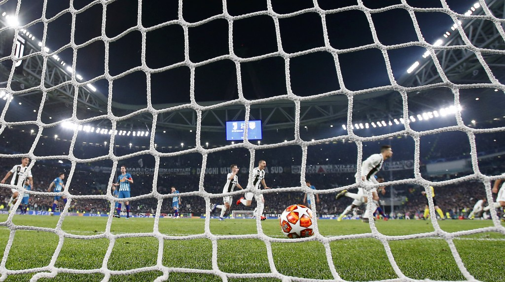 "In this photo taken on Tuesday, March 12, 2019 through a net made by ""La Rete"" factory,  Juventus' Cristiano Ronaldo celebrates after scoring his side"