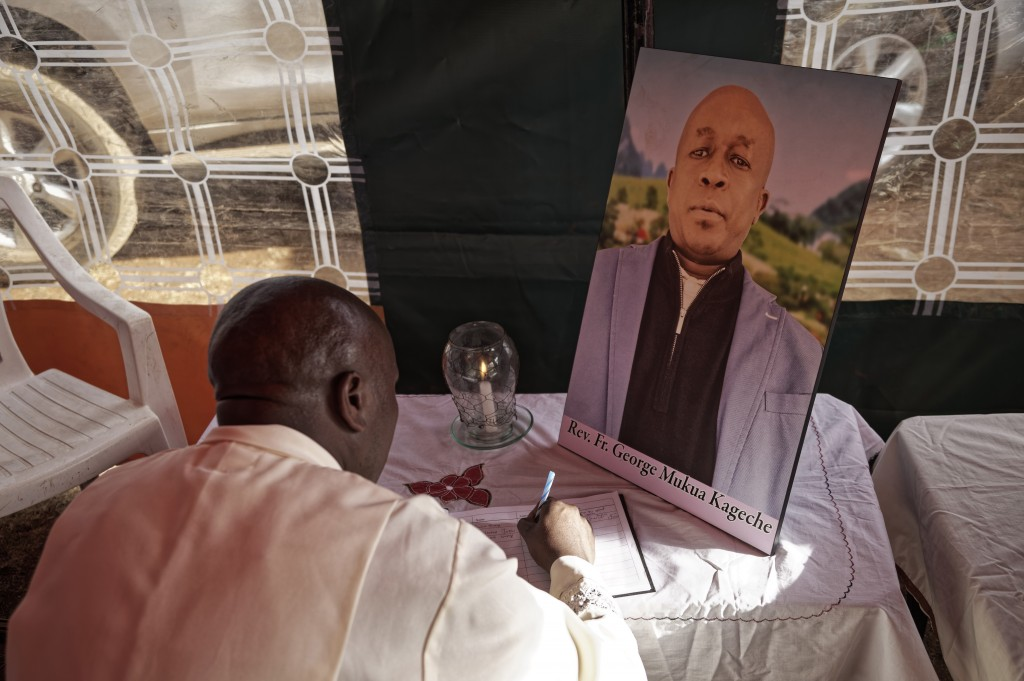 In this photo taken Thursday, March 14, 2019, Father Michael Wa Mugi lights a candle and signs the book of condolence next to a photo of Catholic prie