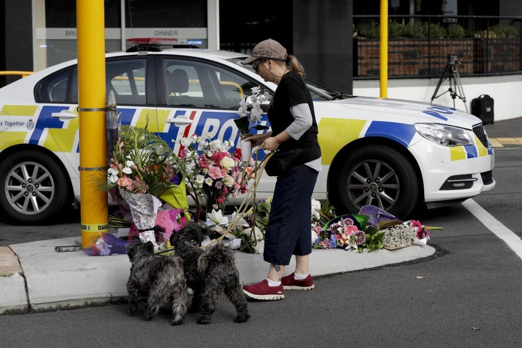 A women places flowers at a makeshift memorial near the Masjid Al Noor mosque in Christchurch, New Zealand, Saturday, March 16, 2019, where one of the