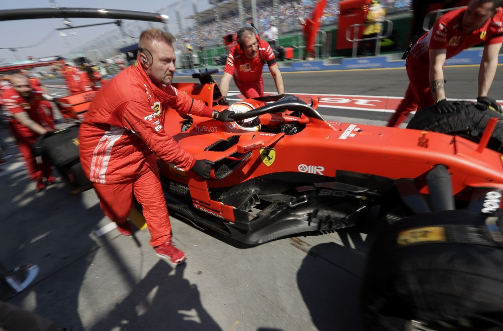 Pit crew for Ferrari driver Sebastian Vettel of Germany push his car in pit lane during the final practice session for the Australian Grand Prix in Me