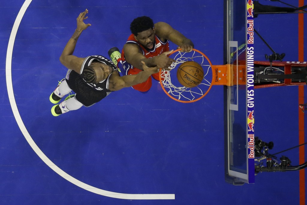 Philadelphia 76ers' Joel Embiid, right, dunks the ball past Sacramento Kings' Harry Giles III during the first half of an NBA basketball game, Friday,