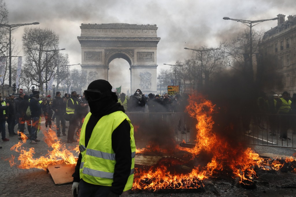 A yellow vest protester walks past a fire on the Champs Elysees avenue Saturday, March 16, 2019 in Paris. French yellow vest protesters clashed Saturd