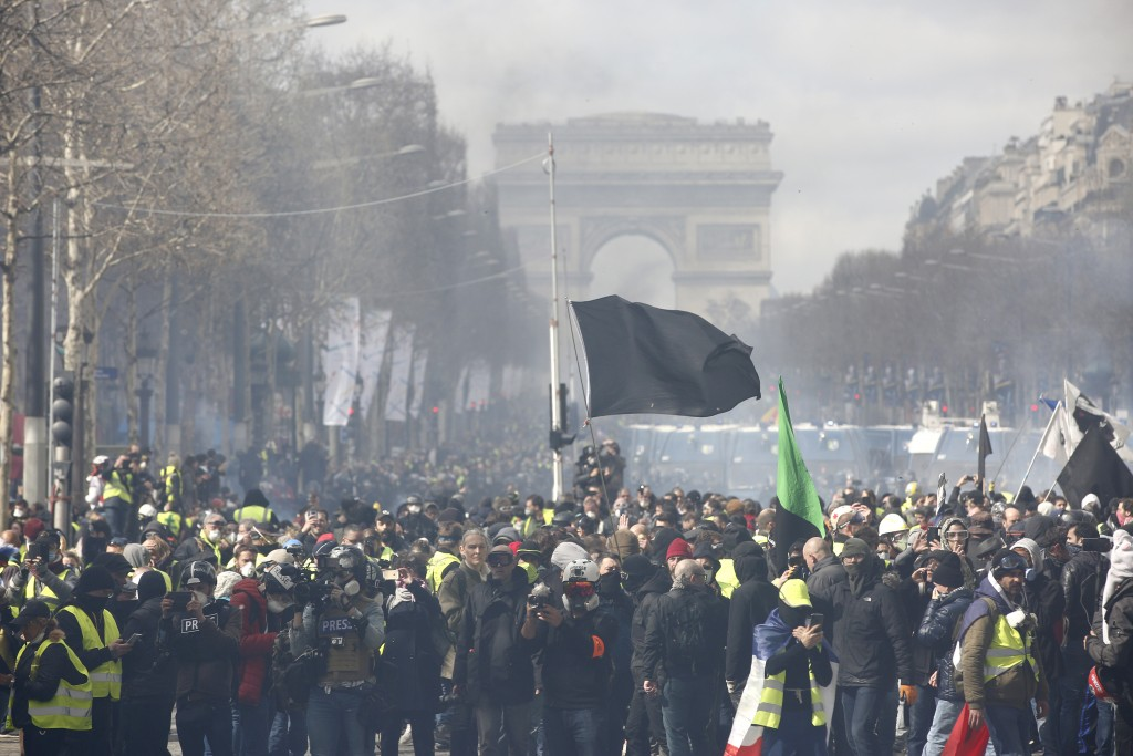 A black flag flies during a yellow vests demonstration on the Champs Elysees avenue Saturday, March 16, 2019 in Paris. French yellow vest protesters c