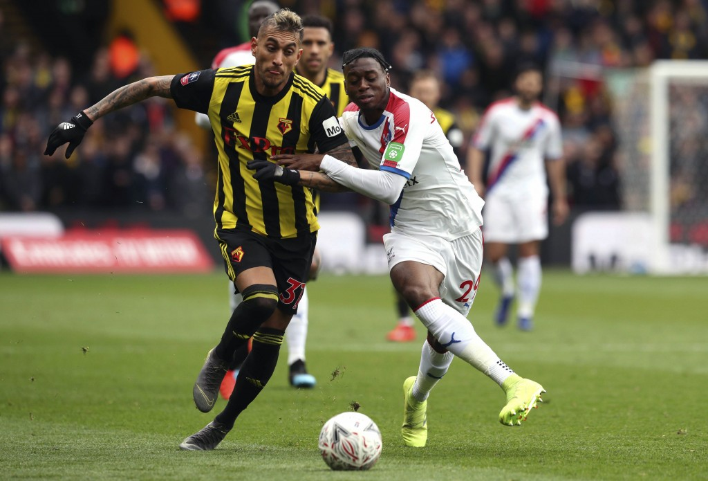 Watford's Roberto Pereyra, left and Crystal Palace's Aaron Wan-Bissaka battle for the ball , during the FA Cup quarter final soccer match between Watf