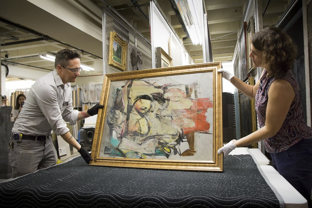 "This August 2017 photo shows ""Woman-Ochre,"" a painting by Willem de Kooning, being readied for examination by University of Arizona Museum of Art staf"
