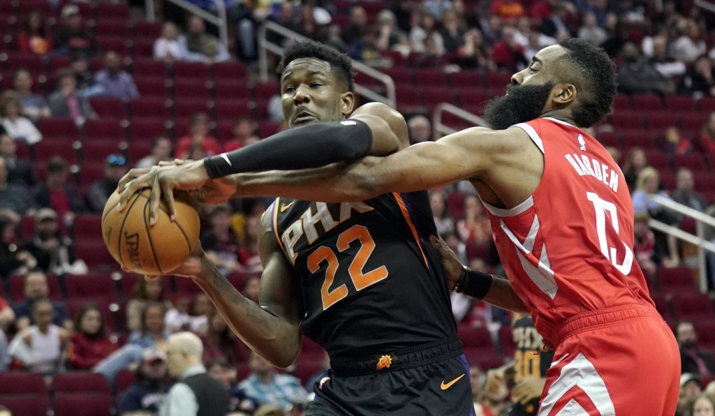Houston Rockets' James Harden (13) tries to steal the ball from Phoenix Suns' Deandre Ayton (22) during the first half of an NBA basketball game Frida