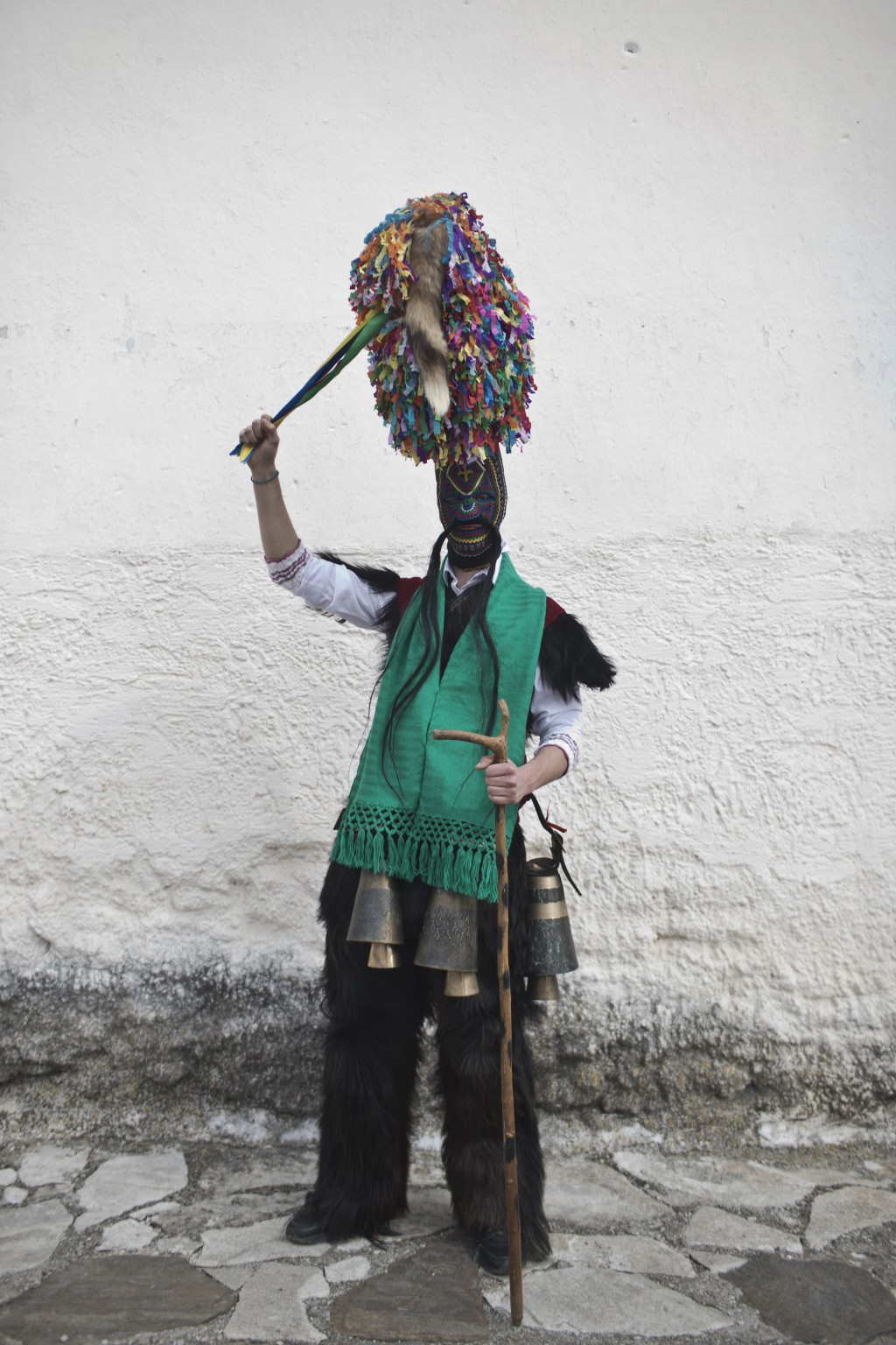 In this Monday March 11, 2019 photo a man wearing a mask that includes a meter- tall, ribbon-covered formation topped with a foxtail poses for a photo