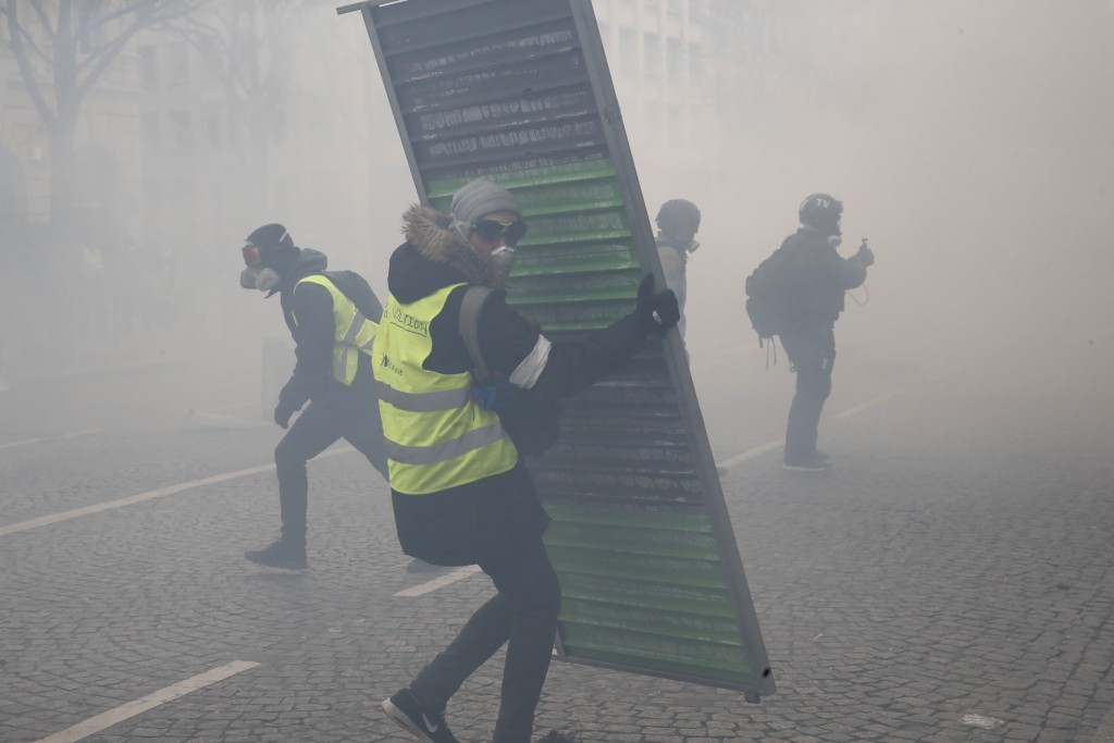 Protesters set up barricades through tear gas during a yellow vests demonstration Saturday, March 16, 2019 in Paris. French yellow vest protesters cla
