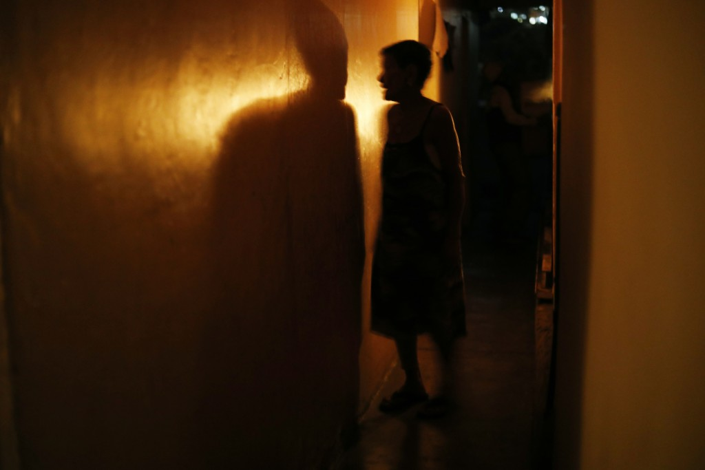 """72-year-old Elizabeth Guzman Espitia navigates a narrow passages up to her windowless room she calls her """"little cave"""" during a blackout in the Santa"""