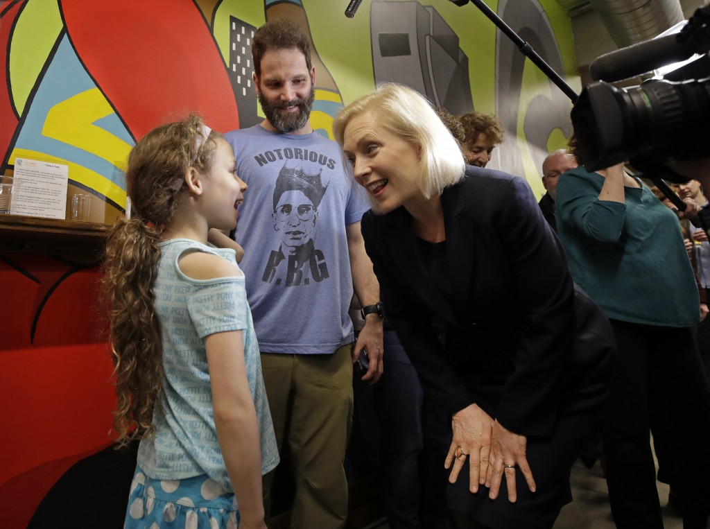 James Porter, of Manchester, N.H., smiles as Democratic presidential candidate Sen. Kirsten Gillibrand, D-N.Y., chats with his 8-year-old daughter, Al