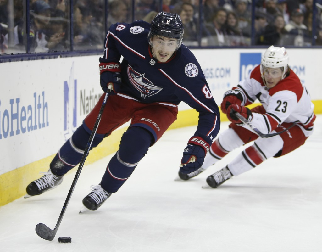 Columbus Blue Jackets' Zach Werenski, left, clears the puck as Carolina Hurricanes' Brock McGinn chases the play during the first period of an NHL hoc