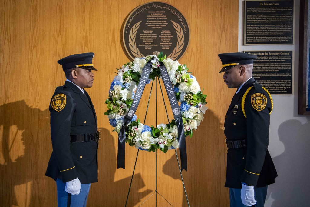 Two United Nations security officers stand beside a memorial wreath during a ceremony at United Nations headquarters, Friday March 15, 2019, for U.N.