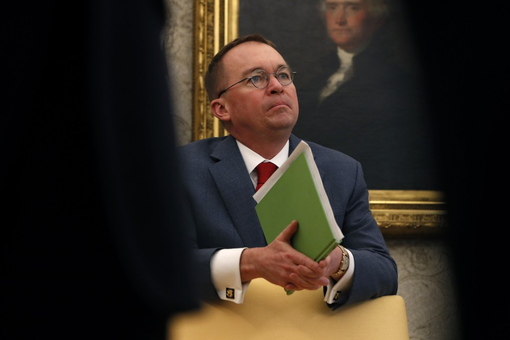 FILE - In this Jan. 31, 2019, file photo, aActing White House chief of staff Mick Mulvaney listens as President Donald Trump speaks during a meeting w