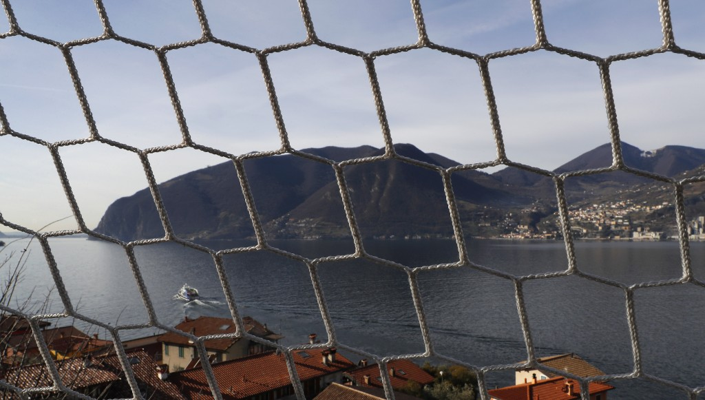 "In this photo taken on Thursday, Feb. 7, 2019, a view of Mont'Isola, Lake Iseo, Northern Italy, taken through a net of ""La Rete"" (The Net) factory in"