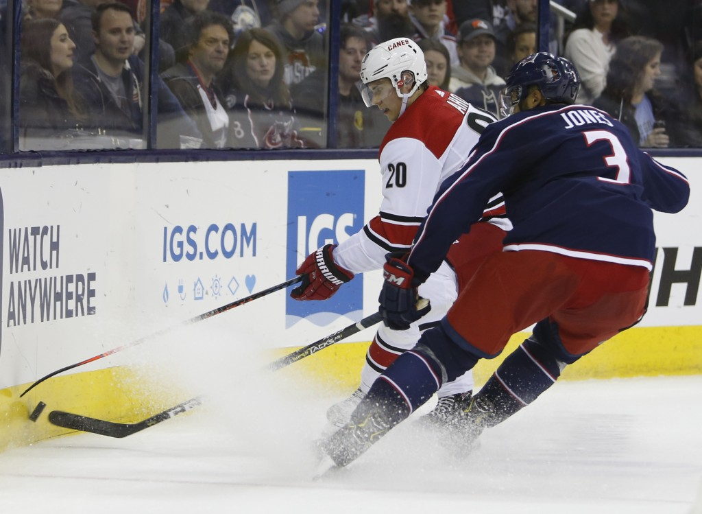 Carolina Hurricanes' Sebastian Aho, left, of Finland, and Columbus Blue Jackets' Seth Jones fight for a loose puck during the first period of an NHL h