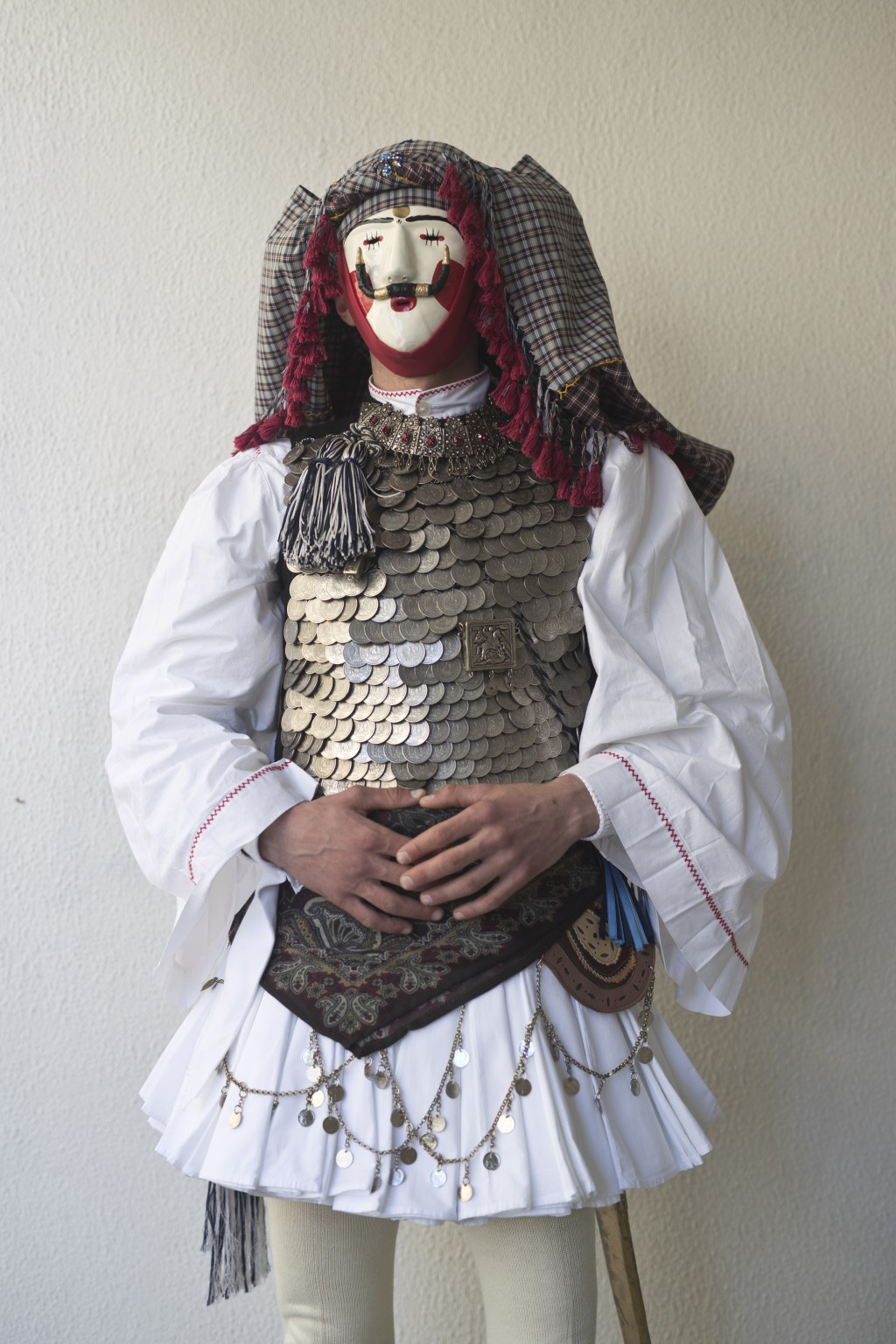 In this Sunday March 10, 2019 photo a dancer wearing a mask and traditional attire poses for a photo,  during the Boules and Genitsaroi carnival parad